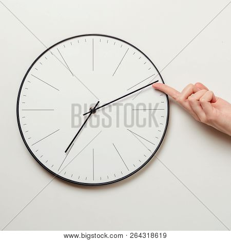 Woman Hand Stop Time On Round Clock, Female Finger Takes Minute Arrow Of The Clock Back, Time Manage