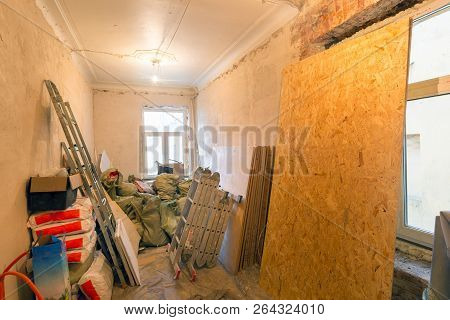 Ladders, bags with putty, construction tools and materials, sheets of drywall are in an  apartment is under construction, remodeling, renovation, extension, overhaul, restoration, home improvement and reconstruction. poster
