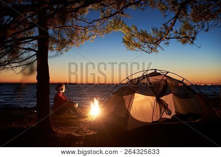Night Camping At Sea Coast Under Clear Blue Sky. Profile Of Smiling Tourist Woman Sitting Alone At C