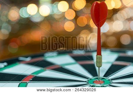 Red Dart Target Arrow Hitting On Bullseye Over Bokeh Light Background Vintage Tone,metaphor To Accur