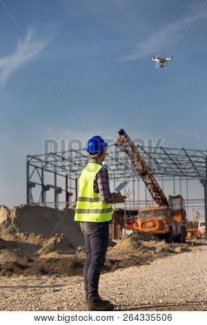 Rear View Of Engineer Controlling Drone Above Building Site With Metal Construction And Crane In Bac