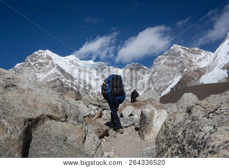 Unidentified Tourist And Porter Walking On The Road To Everest Base Camp In Sagarmatha National Park