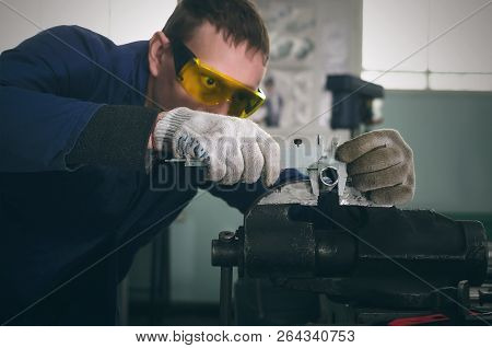 Man worker is working with iron detail on vise grip on blacksmith table and is measuring a diameter of machine part by caliper. poster