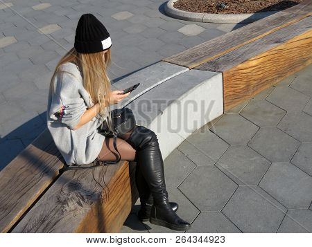 Teen Girl In A Black Cap And Jackboots Sitting With A Smartphone In Hands On The Street. Concept For