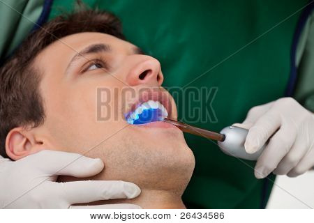 Patient having dental checkup with ultraviolet light at dentist's clinic
