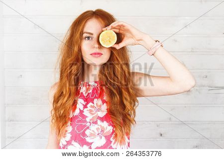 Delighted Red-hair Woman Keep Two Lemons On Her Eyes. The Portrait With A Copyspace