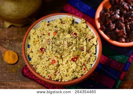 high angle view of an earthenware bowl with tabbouleh, a typical levantine arab salad, on a table set for lunch or dinner, next to a golden teapot and a bowl with sun-dried tomato