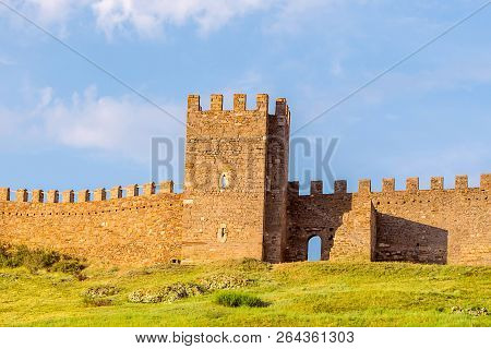 Ruins Of The Old Tower Genoese Fort Fort A Crenellated Wall On Top Of A Green Hill An Old Stone Buil