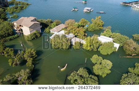 poster of Mansions and Luxury homes flooded and destroyed by climate change and rising water level , aerial drone view looking down from house that is half way under water. Extreme flooding event , natural disaster , flood insurance , home owners insurance