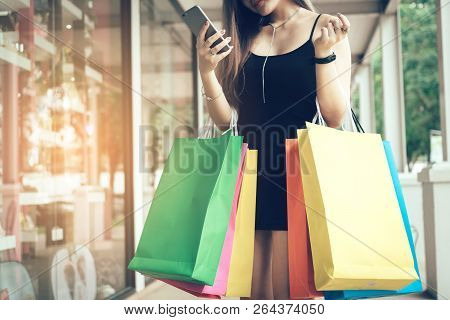 Woman Using Smartphone And Checking Sale Promotion With Holding Shopping Bags.
