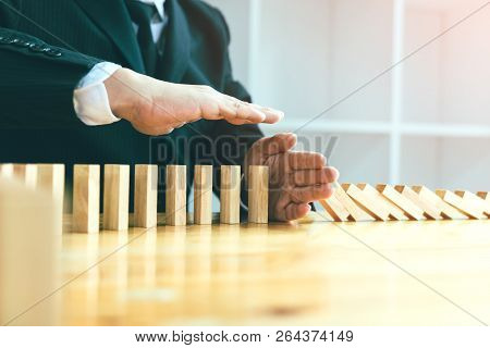 Risk Concept With Hand Of Businessman Stopping And Protection The Domino Effect.