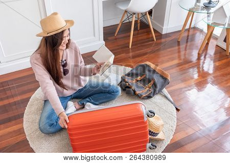 Young Asian Woman Traveler Prepare Things Into Orange Suitcase For Holiday Vacation At Home.backpack