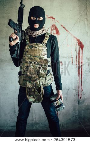 A Terrorist Wearing A Hat To Hide His Face And Carrying M-16 Assault Rifle Gun, He Is Holding A Gun