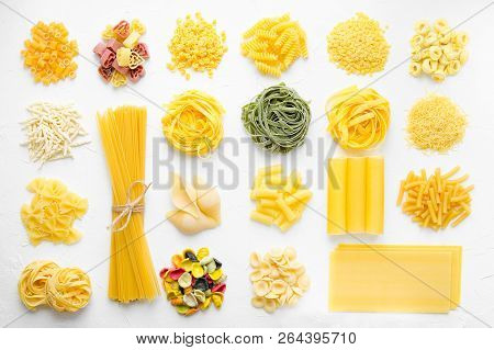 Variety Of Types And Shapes Of Italian Pasta In Rows On White Background From Above. Italian Cuisine