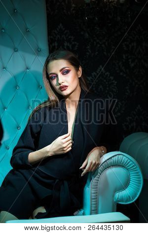 Beautiful Girl In A Black Coat On A White Leather Chair