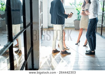 Partial View Of Business Colleagues Having Conversation In Hall During Coffee Break
