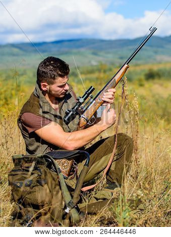 Hunter khaki clothes ready to hunt nature background. Hunting shooting trophy. Hunter with rifle looking for animal. Hunting hobby and leisure. Man charging hunting rifle. Hunting equipment concept poster