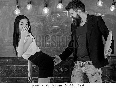 Schoolmaster punishes sexy student with slapping on her buttocks. Girl on guilty and helpless face punished by teacher. Man with beard slapping sexy student, chalkboard on background. Sex game concep poster
