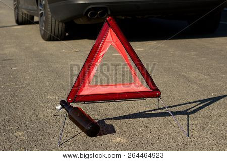 An Empty Bottle Of Beer Or Other Alcohol And A Warning Triangle.empty Bottle Of Beer Or Other Alcoho
