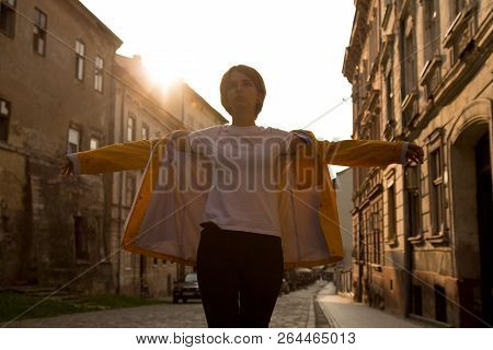 Young Careless Girl In Yellow Raincot Walking In City. Being In A Good Mood. Teenage Fashion Concept