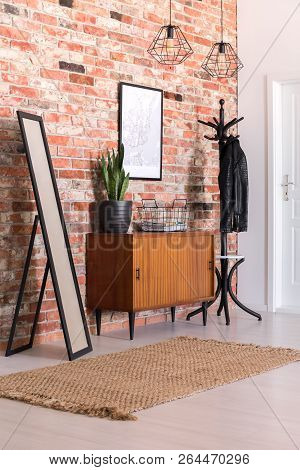 Classic Corridor With Brick Wall, Clothes Hanger, Cupboard, Carpet And Mirror, Real Photo