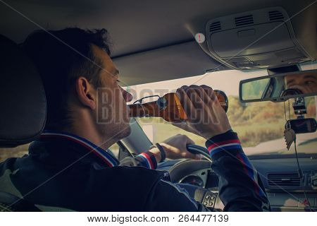 A drunken man driving a car with a bottle of alcohol in his hand.A man holds a driving wheel and a bottle of beer. poster