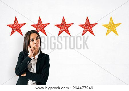 Portrait Of Attractive Thoughtful Young European Woman On Concrete Background With Drawn Five Stars.