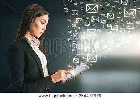 Side View Of Young European Businesswoman Using Tablet With Abstract Emails. E-mail Marketing Concep