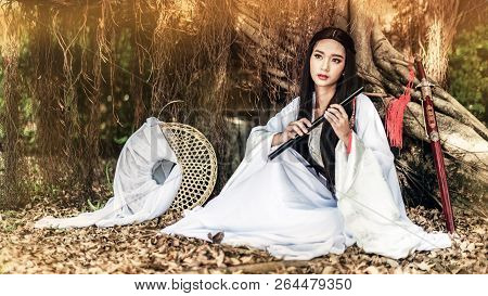 Beautiful Chinese Woman With A Traditional Suit With A Flute In Her Hands, Beautiful And Belligerent