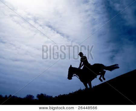 Silhouette of a horseman riding downhill