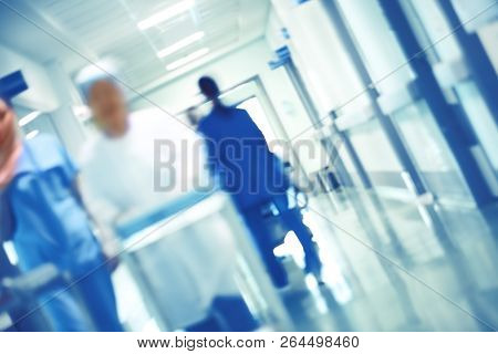 Blurred Figures Of Walking Medical Staff In The Hospital Hallway, Unfocused Background.