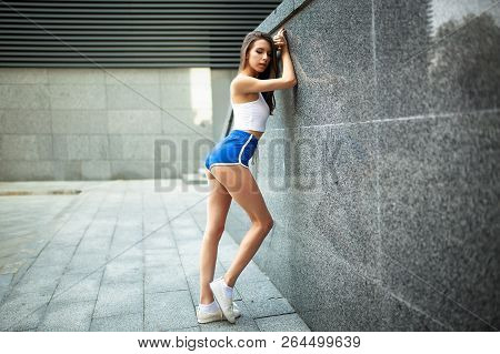 Beautiful Young Sexy Girl Athlete Resting After A Hard Athletic Workout On A City Street. Female Ath
