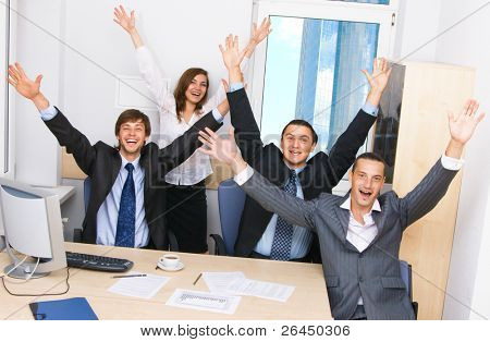 Joyful business team in office celebrating in office