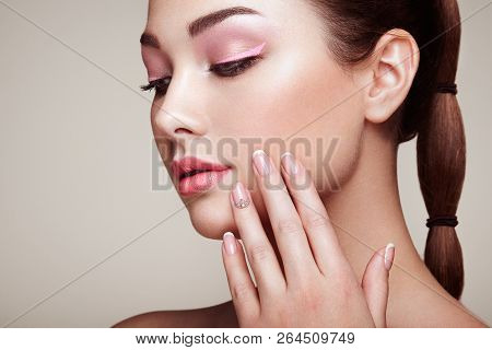 Beauty Brunette Woman With Perfect Makeup. Red Lips And Nails. Perfect Eyebrows. Skin Care Foundatio
