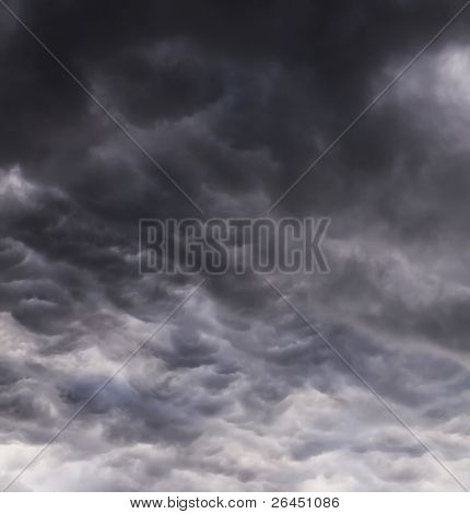 Dark stormy sky with silver gleams of sunlight