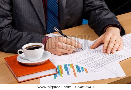 Businessman working at table covered with documents