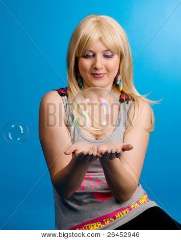 Young woman with a large soap bubble, blue background