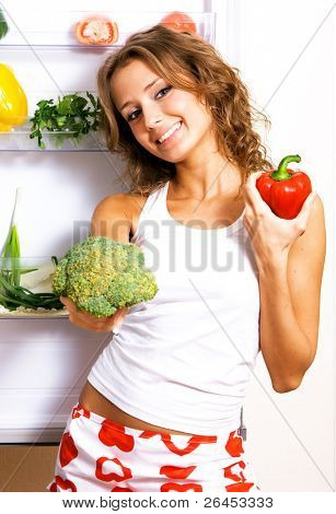Cheerful young woman taking vegetables out of fridge