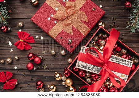 a christmas gift money packed with red slack xmas items on a wooden