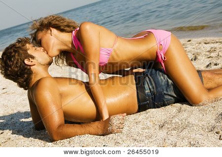 Young passionate couple kissing on the sand