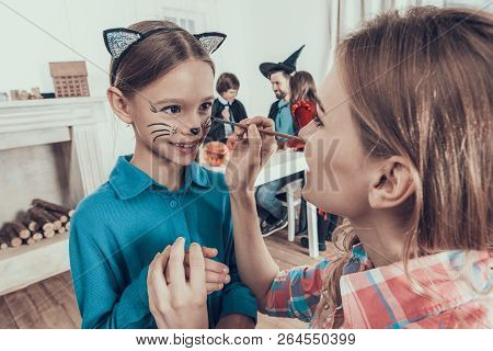 Mother Helping Daughter With Costume For Halloween. Adult Woman Putting On Makeup On Smiling Young G
