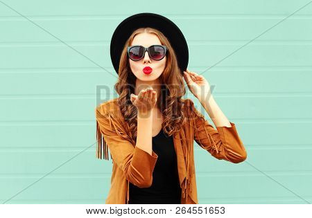 Fashion Portrait Pretty Woman Sends Air Sweet Kiss In Black Round Hat, Sunglasses On Gray Wall Backg