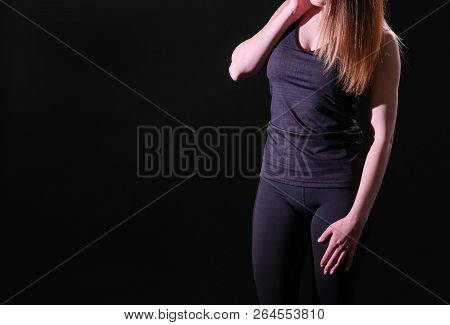 Athletic Girl In Tight Sportswear. Black Background.