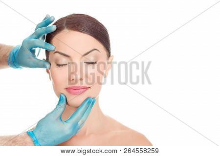 Woman with eyes closed after aesthetic surgery, smiles while the doctor shows the results isolated on white background with copy space. Doctor hands around patient face. Beautify concept poster