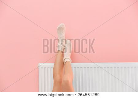 Woman Warming Legs On Heating Radiator Near Color Wall, Closeup. Space For Text