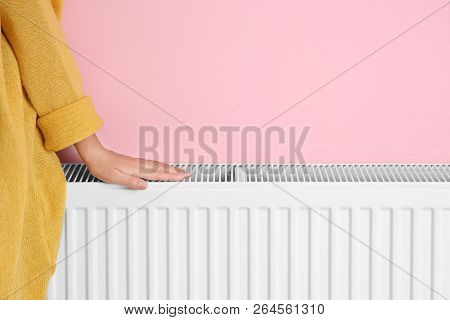 Woman Warming Hand On Heating Radiator Near Color Wall