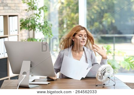 Businesswoman Suffering From Heat In Front Of Small Fan At Workplace