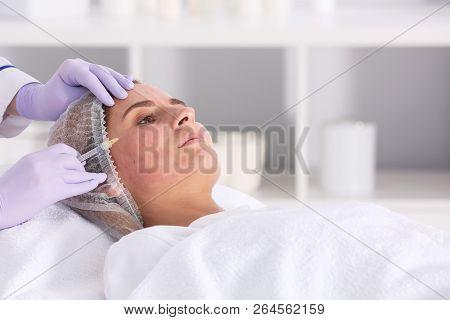Woman undergoing face biorevitalization procedure in salon. Cosmetic treatment poster