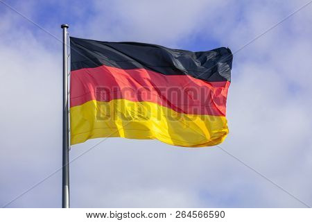 German flag waving on silver flagpole. Blue sky with many white clouds background.