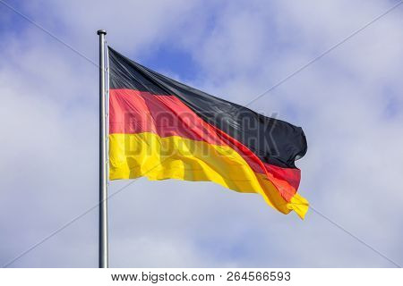 German flag waving on flagpole. Blue sky with many white clouds background.